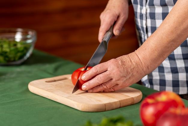 De vrouwen scherpe tomaten van de close-up