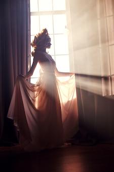 De vrouwen van de silhouetmanier dichtbij het venster in de zon.