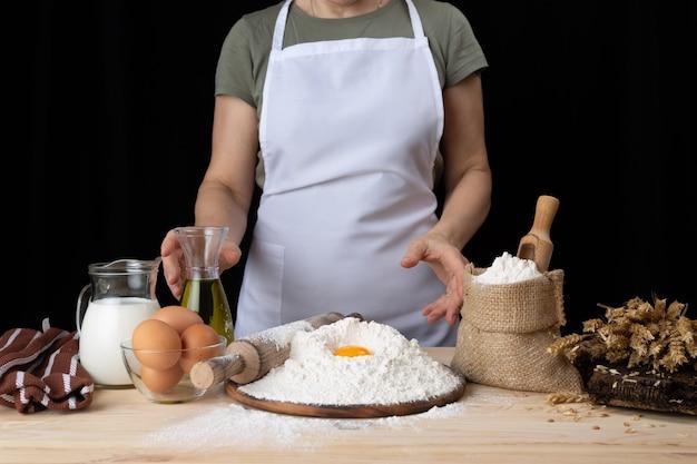 De vrouwenbakker bereidt gebakjes met recept voor
