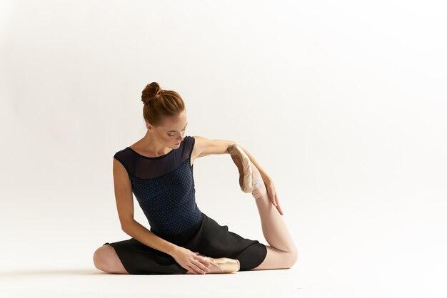 De vrouwenballerina rekt zich in de studio uit