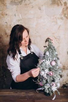De vrouwenbloemist doet boeket van bloemen nieuw jaar en kerstmis deciration