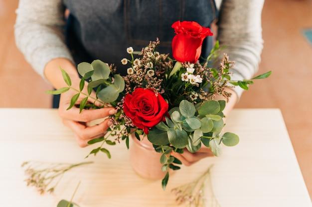 De vrouwenbloemist maakt een rood rozenboeket op houten lijst