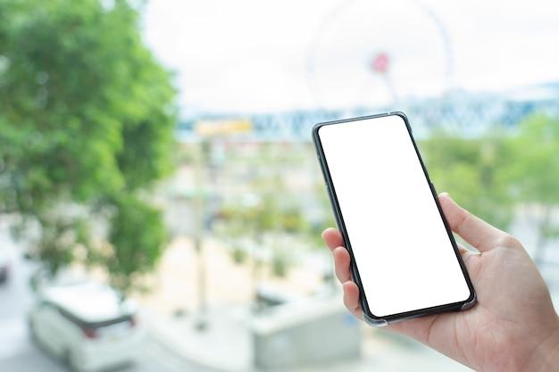 De vrouwenhand die mobiele smartphones houden isoleerde het witte scherm