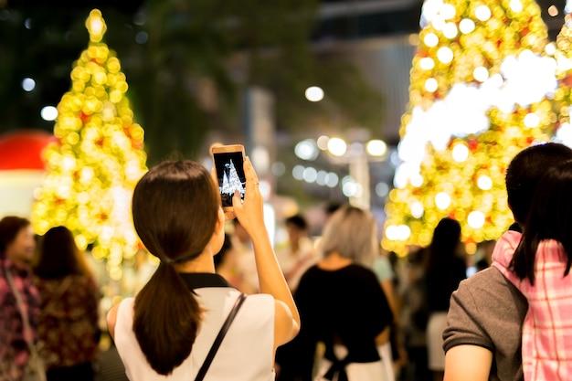 De vrouwenhand die mobiele telefoon houden neemt een foto van kerstmisboom en licht.