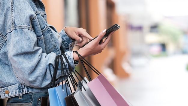 De vrouwenhand die van de close-up mobilofoon in het winkelen gebruikt.