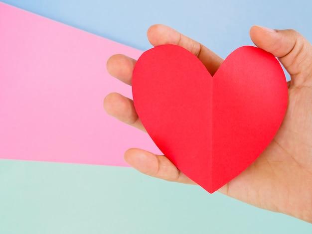 De vrouwenhand die van de close-up rood document hart houdt