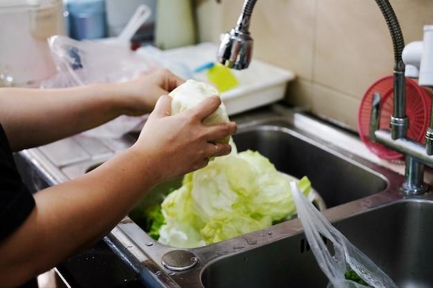De vrouwenhand die van de close-up verse groene groenten in de keukengootsteen wast.