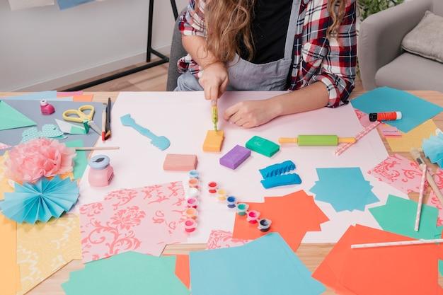 De vrouwenhand die van de kunstenaar kleurrijke klei snijdt die kleisnijder op lijst gebruikt