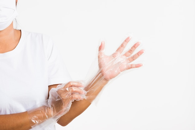 De vrouwenhand die voor eenmalig gebruik dragen beschermt wegwerp doorzichtige plastic handschoen