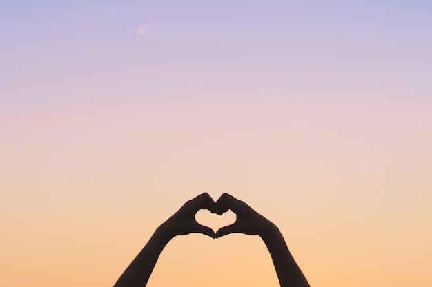 De vrouwenhand doet hartvorm op blauwe hemel en bokeh achtergrond.