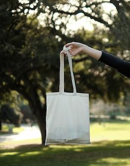 De vrouwenhand draagt de eco katoenen zak