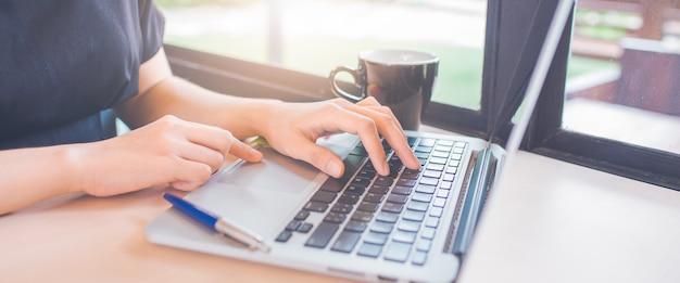 De vrouwenhand gebruikt een laptop computer in bureau.