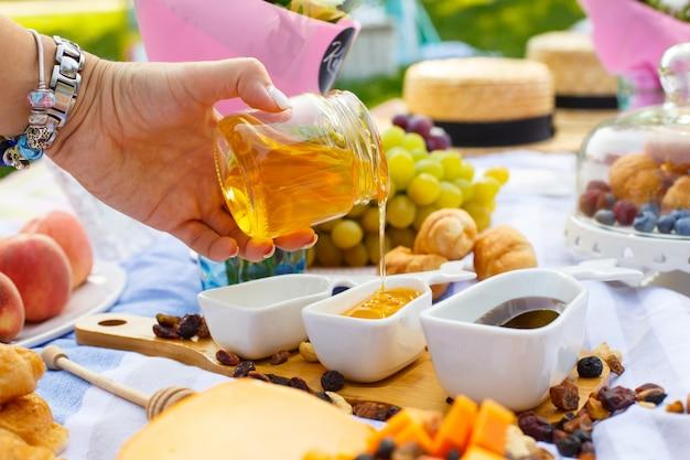 De vrouwenhand giet honing van transparante fles aan sauceboat, bij de achtergrond van de de zomerpicknick