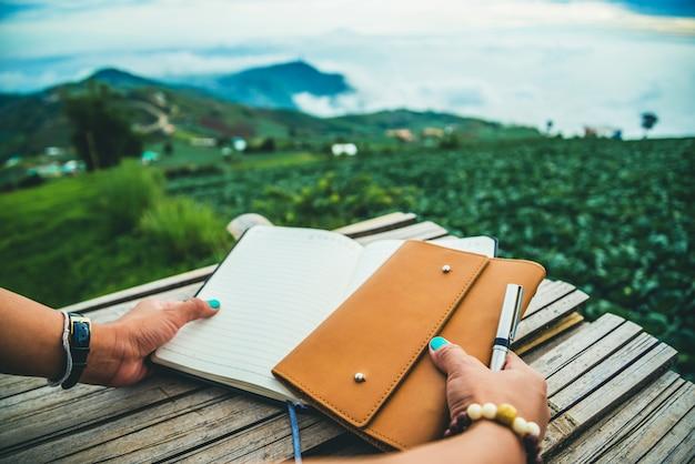 De vrouwenhand houdt de geschriften vast. ochtendsfeer de bergen zijn mistig. phetchabun phutubberg