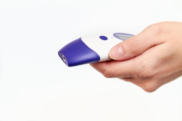 De vrouwenhand houdt een elektronische contactloze thermometer