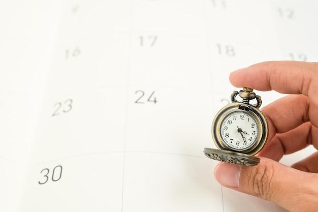 De vrouwenhand houdt een klassiek uitstekend halsbandhorloge op het document van de kalenderdatum