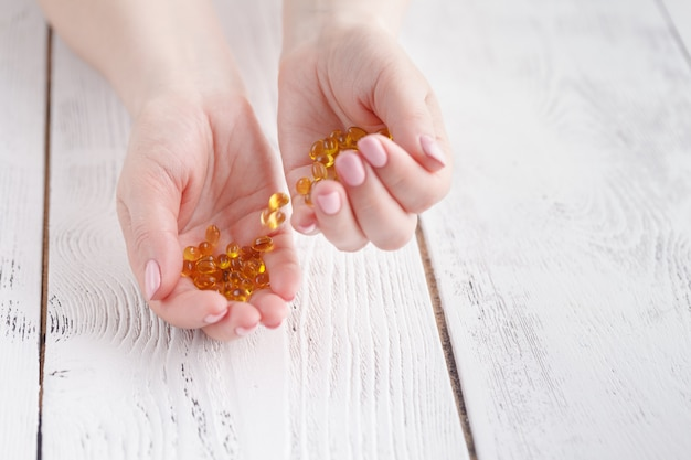 De vrouwenhand houdt gele medicijncapsules van omega 3, gezonde supplementpillen