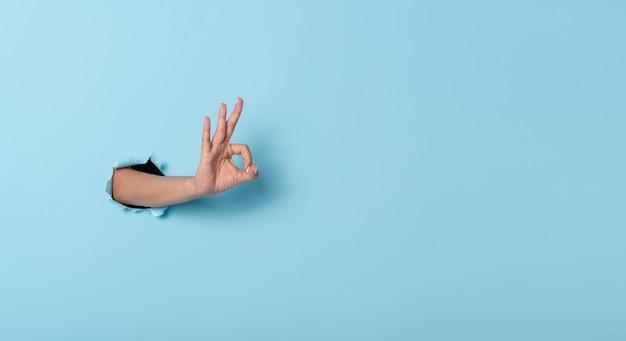 De vrouwenhand maakt een gebaar ok in de muur op blauwe bannerachtergrond.