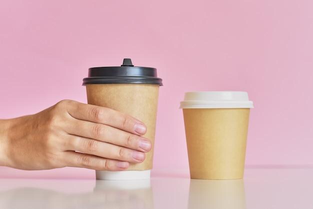 De vrouwenhand neemt van twee koffiedocument kop op roze achtergrond over