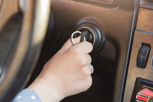 De vrouwenhand op autosleutel, probeert motor te starten, zet sleutel in sleutelgat, autopaneel en wiel op achtergrond aan. sleutel in slot gestoken. beginnende reis. auto concept starten