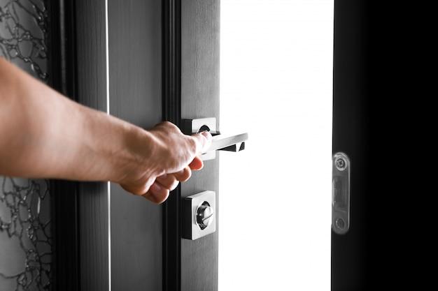 De vrouwenhand opent de zwarte houten deur