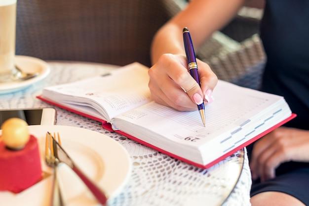 De vrouwenhand schrijft businessplan op klein notitieboekje bij openluchtgebied bij koffie.