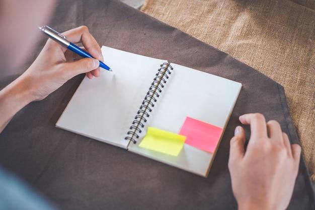 De vrouwenhand schrijft op een lege blocnote met een pen, op een bruin tafelkleed.