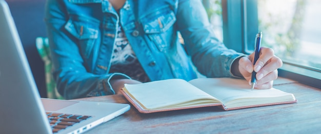 De vrouwenhand schrijft op notitieboekje met een pen in het bureau.