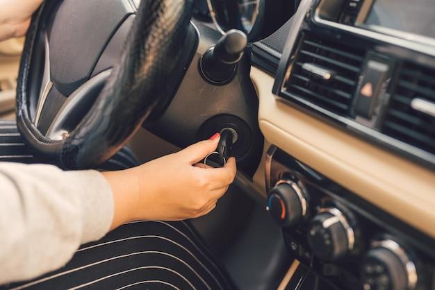 De vrouwenhand steekt de sleutel in het contact en start de motor van de auto