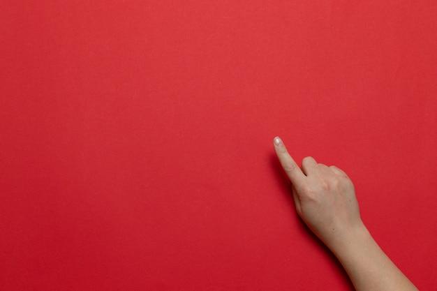 De vrouwenhand toont hand met wijsvinger omhoog voor punt iets geïsoleerd op rode achtergrond. plat lag stijl samenstelling