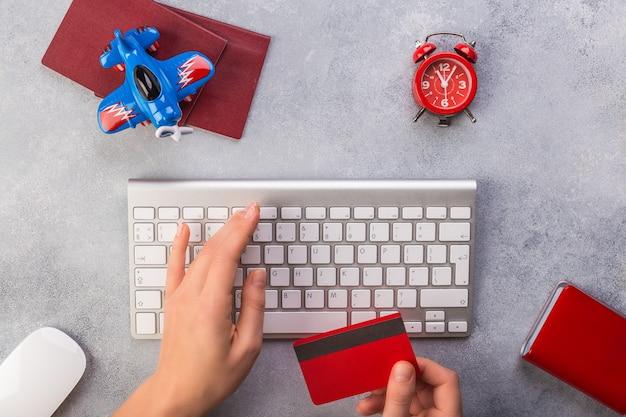 De vrouwenhand typt toetsenbord en neemt creditcard dichtbij kleine vliegtuigklok en paspoorten