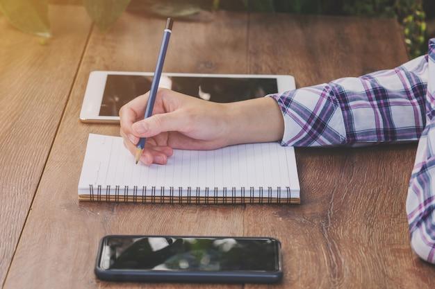 De vrouwenhand van azië het schrijven notitieboekje op houten lijst in koffiewinkel.