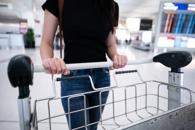 De vrouwenhand van close-up duwt de kar met koffers op de luchthaven.