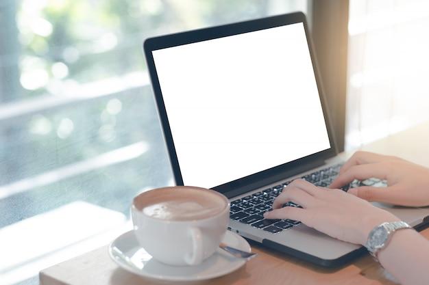 De vrouwenhand van de close-up het typen toetsenbordcomputer die het witte scherm in koffiewinkel tonen