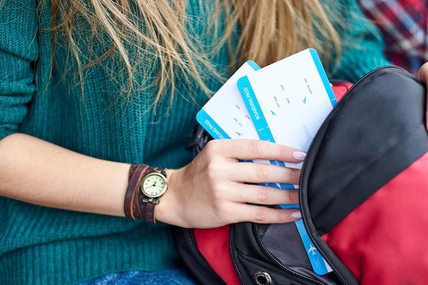 De vrouwenhand zette een instapkaart in zak. hand met kaartjes. wachten op vliegtuig en reizen