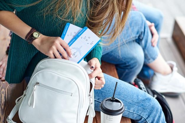 De vrouwenhand zette een instapkaart in zak. hand met kaartjes. wachten op vliegtuigen en reizen