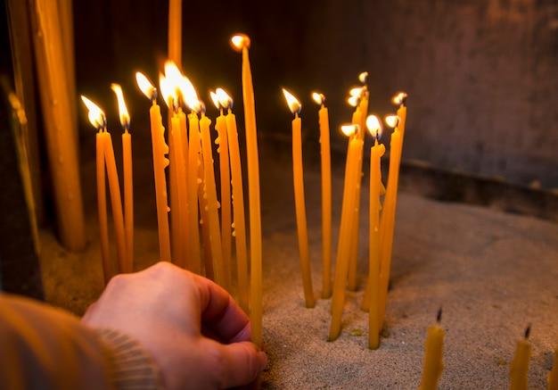 De vrouwenhand zette kaars op vlam voor bidt in kerk. bijenwaskaarsen branden in tempel