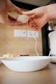 De vrouwenhanden breekt kippeneieren in een kom in de keuken.