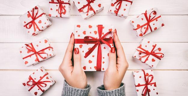 De vrouwenhanden geven de verpakte doos van de vakantiegift