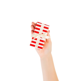 De vrouwenhanden geven kerstmis met de hand gemaakt geïsoleerd heden