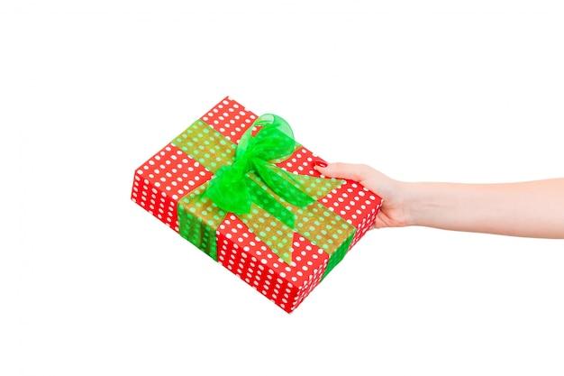 De vrouwenhanden geven verpakt kerstmis of ander met de hand gemaakt heden van de vakantie in rood document met groen lint