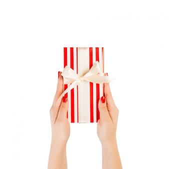 De vrouwenhanden geven verpakt kerstmis of ander vakantie met de hand gemaakt heden in rood document met gouden lint.