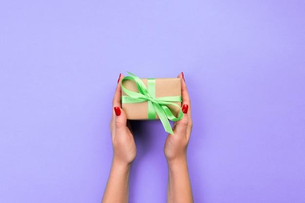 De vrouwenhanden geven verpakte valentijnskaart of ander vakantie met de hand gemaakt cadeau in document met groen lint.