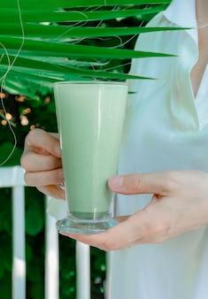 De vrouwenhanden houden kop groene matcha latte van het de theeglas van de koffiethee tropische bladeren