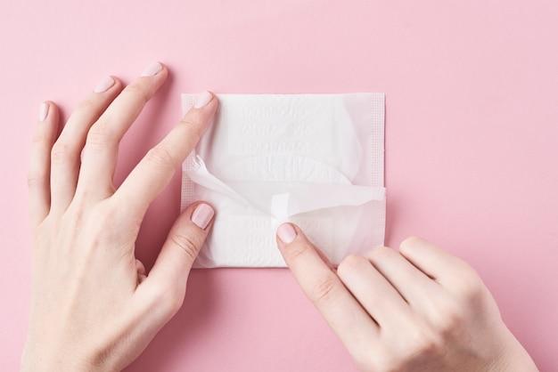 De vrouwenhanden houden maandverband op een roze