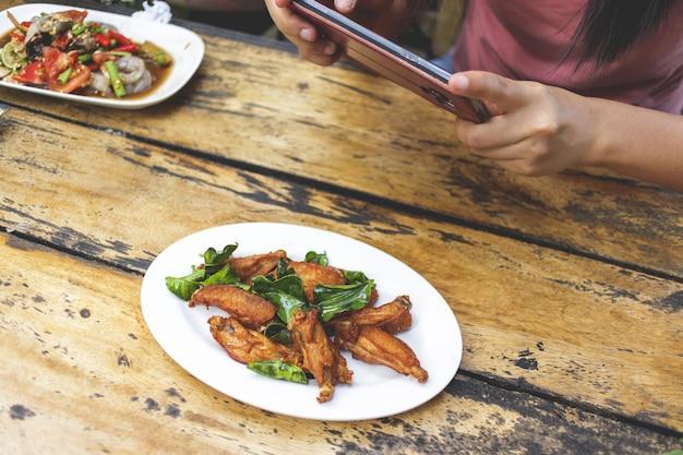 De vrouwenhanden neemt foto van lokaal thais voedsel op lijst met smartphone