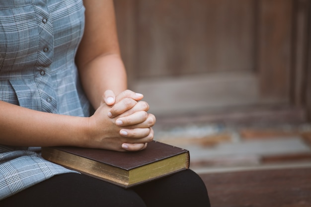 De vrouwenhanden vouwden in gebed op een heilige bijbel voor geloofsconcept in uitstekende kleurentoon