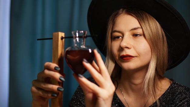 De vrouwenheks bereidt een drankje voor. rode liefdesdrank in een hartvormige glazen pot. liefde magisch concept