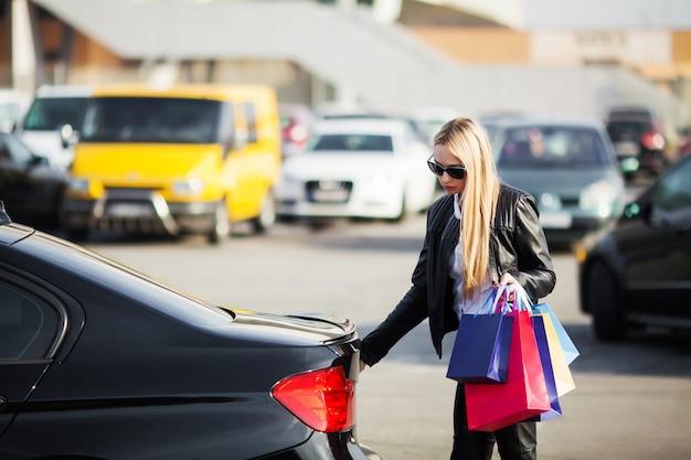 De vrouwenholding kleurde zakken dichtbij haar auto in zwarte vrijdagvakantie