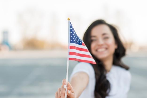 De vrouwenholding van de close-upvlag van de vs het glimlachen